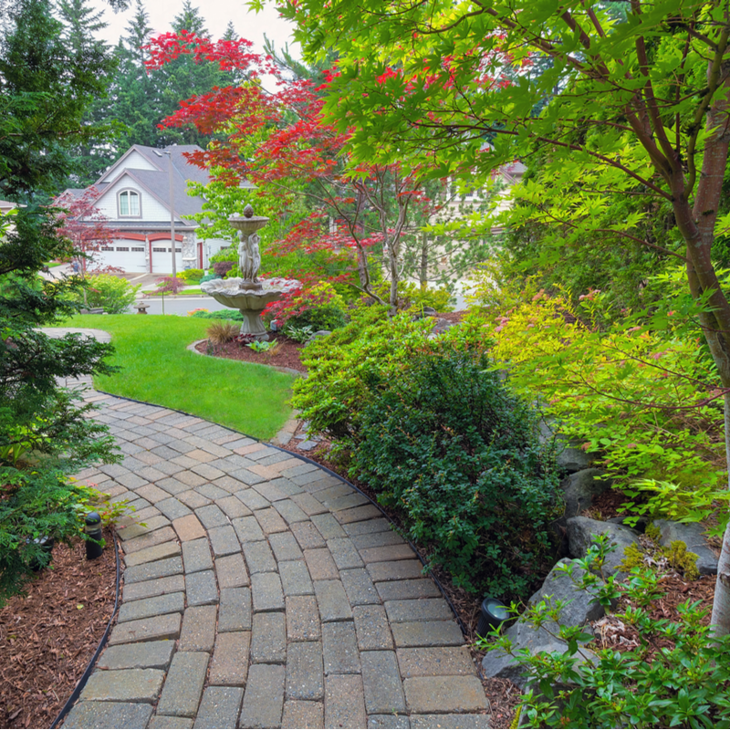 paver path through green landscaping leading to a home
